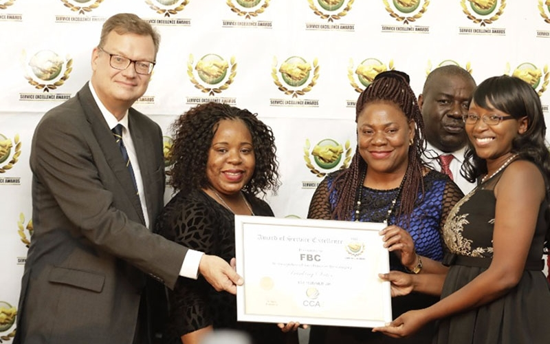 Faideth Foto (FBC Bank Operations Manager Convenience Banking- third from left), Sharon Tapesa (Call Centre CSO-second from left) and Laurinda Chiguvare (Call Centre Officer) receive the award from Dr Thorsten Hutter (German Ambassador to Zimbabwe-far left).